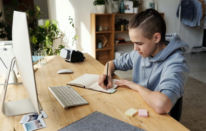 boy-in-gray-hoodie-while-writing-on-his-notebook-4144531